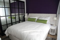 Slaapkamer met grote duble bed en muurspiegel Royalty-vrije Stock Foto