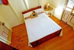 Slaapkamer met opgepoetste houtvloeren stock afbeeldingen