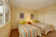 Slaapkamer met twee eenpersoonsbedden in vrolijk beddegoed Stock Fotografie