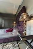 Slaapkamer met viooltje gewatteerd bed stock afbeelding