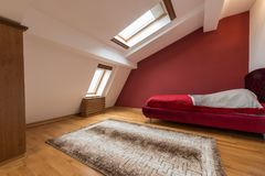 Slaapkamerbinnenland in luxe rode zolder, zolder, flat met dak stock afbeeldingen