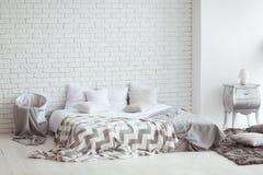 Slaapkamerbinnenland met een bakstenen muur met een bed en bedlijsten Royalty-vrije Stock Afbeelding