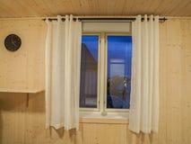 Slaapkamervenster met wit transparant gordijn in houten muur stock afbeelding