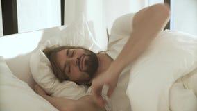 Slaapmens in Bed met Witte Linens bij Lichte Slaapkamer stock videobeelden