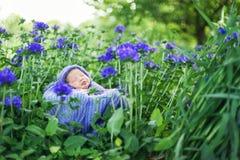 slaapt de 17 dag oude Glimlachende pasgeboren baby op zijn maag in de mand op aard in de tuin openlucht Stock Afbeeldingen