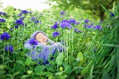 slaapt de 17 dag oude Glimlachende pasgeboren baby op zijn maag in de mand op aard in de tuin openlucht Stock Afbeelding