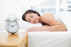Slaapvrouw met vage wekker in voorgrond Royalty-vrije Stock Foto
