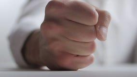 Slaat de close-up agressieve bediende zijn vuist op de lijst De manifestatie van agressie op het werk in het bureau stock videobeelden