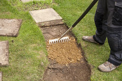 Slab Laying. Person preparing ground for laying a slab path royalty free stock images