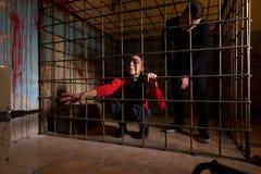 Slachtoffers in een metaalkooi worden gevangengenomen, meisje die haar hand trekken die throug stock afbeelding