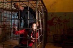 Slachtoffers van paar de bange die Halloween in een looki van de metaalkooi worden gevangengenomen royalty-vrije stock fotografie