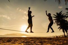 少年在海滩的夫妇平衡的slackline 免版税库存照片