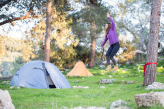 Slackline balancing young woman equilibrium exercise forest. Young woman balance equilibrium exercising forest camping tents lifestyle sports Stock Photography