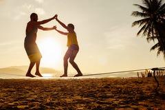 Slackline d'equilibratura delle coppie adolescenti sulla spiaggia Fotografia Stock Libera da Diritti
