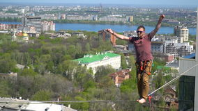 Slackline between tall buildings stock video