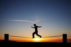 Slackliner в заходе солнца Стоковые Фото