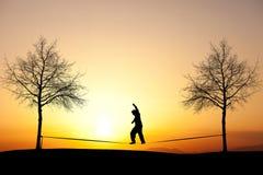 Slackliner en puesta del sol Fotografía de archivo