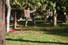Slacklining在公园 免版税库存图片