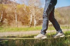 Slacklining är en övning av att balansera, som nylon- eller polyestertyg som sträcks mellan två ankarpunkter, är i royaltyfri fotografi