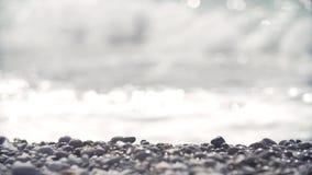 Slag för havsvattenvågor på kusten som täckas i kiselstenstenar stock video