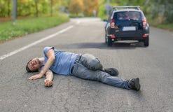 Slag- och körningsbegrepp Sårad man på vägen framme av en bil arkivbild
