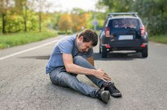 Slag- och körningsbegrepp Sårad man på vägen framme av en bil arkivbilder
