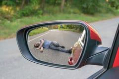 Slag- och körningsbegrepp Sikt på sårad man på vägen i bakre spegel av en bil royaltyfri foto