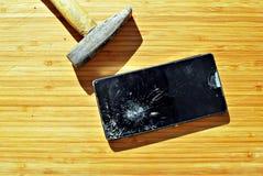 Slagen telefonskärm på en tabell med en hammare Royaltyfria Bilder