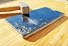 Slagen telefonskärm på en tabell med en hammare Arkivfoton