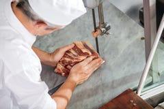 Slager Cutting Fresh Meat met Lintzaag Royalty-vrije Stock Afbeeldingen