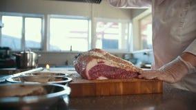 Slager die kruiden toevoegen in brok die van vers ruw vlees op een houten raad in een commerciële keuken, langzame motie liggen stock video