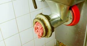 Slager die maken die in de machine 4k wordt fijngehakt van de vleesgehaktmolen stock videobeelden