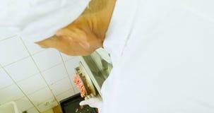 Slager die maken die in de machine 4k wordt fijngehakt van de vleesgehaktmolen stock footage