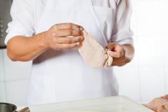 Slager Holding Chicken Meat Omvat met Bloem Royalty-vrije Stock Afbeeldingen