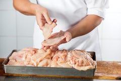 Slager Holding Chicken Pieces bij Teller Royalty-vrije Stock Afbeeldingen
