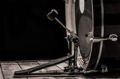 slaginstrument, bastrommel met pedaal op houten raad met een zwarte achtergrond Stock Fotografie