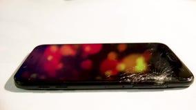 Slagit exponeringsglas av mobiltelefonen på tabellen som roterar i ljus med halva den brutna skärmen och ramböjelsen stock video