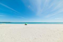 Slags solskydd och livfartyg i en tom strand Arkivfoton