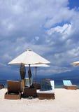 Slags solskydd och solen bäddar ned på varm vit sand Royaltyfria Foton