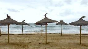 Slags solskydd på den sandiga stranden efter den turist- säsongen arkivfilmer