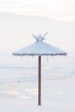 Slags solskydd som täckas med snö på stranden i vintern Arkivfoto
