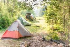 Slags tvåsittssoffa som campar med tält och en bil Arkivbild