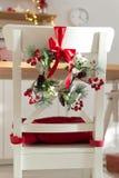 Slags tvåsittssoffa som dekoreras med julpynt med röd vit köksstol för band- och granfilialer royaltyfria bilder