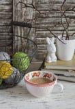 Slags tvåsittssoffahemplatsen med en korg med garn, staplade böcker, vasen med torra filialer, en keramisk kanin och en kopp te m Arkivbild
