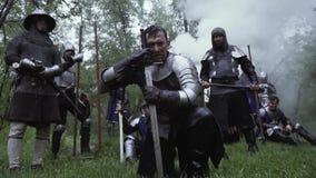 Slagveld in de bos, middeleeuwse militairen met wapens en metaalpantser stock videobeelden