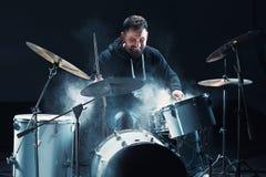 Slagwerker die op trommels vóór rotsoverleg repeteren De muziek van de mensenopname bij het drumstel in studio stock fotografie