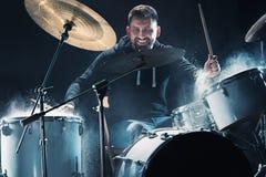 Slagwerker die op trommels vóór rotsoverleg repeteren De muziek van de mensenopname bij het drumstel in studio royalty-vrije stock afbeeldingen