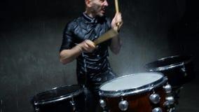 Slagwerker het spelen trommels met water in een donkere studio stock footage
