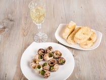 Slakken als gastronomisch voedsel met brood en wijn stock foto's