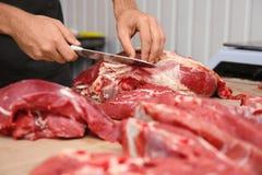 Slaktare som klipper nytt rått kött på räknare arkivfoto